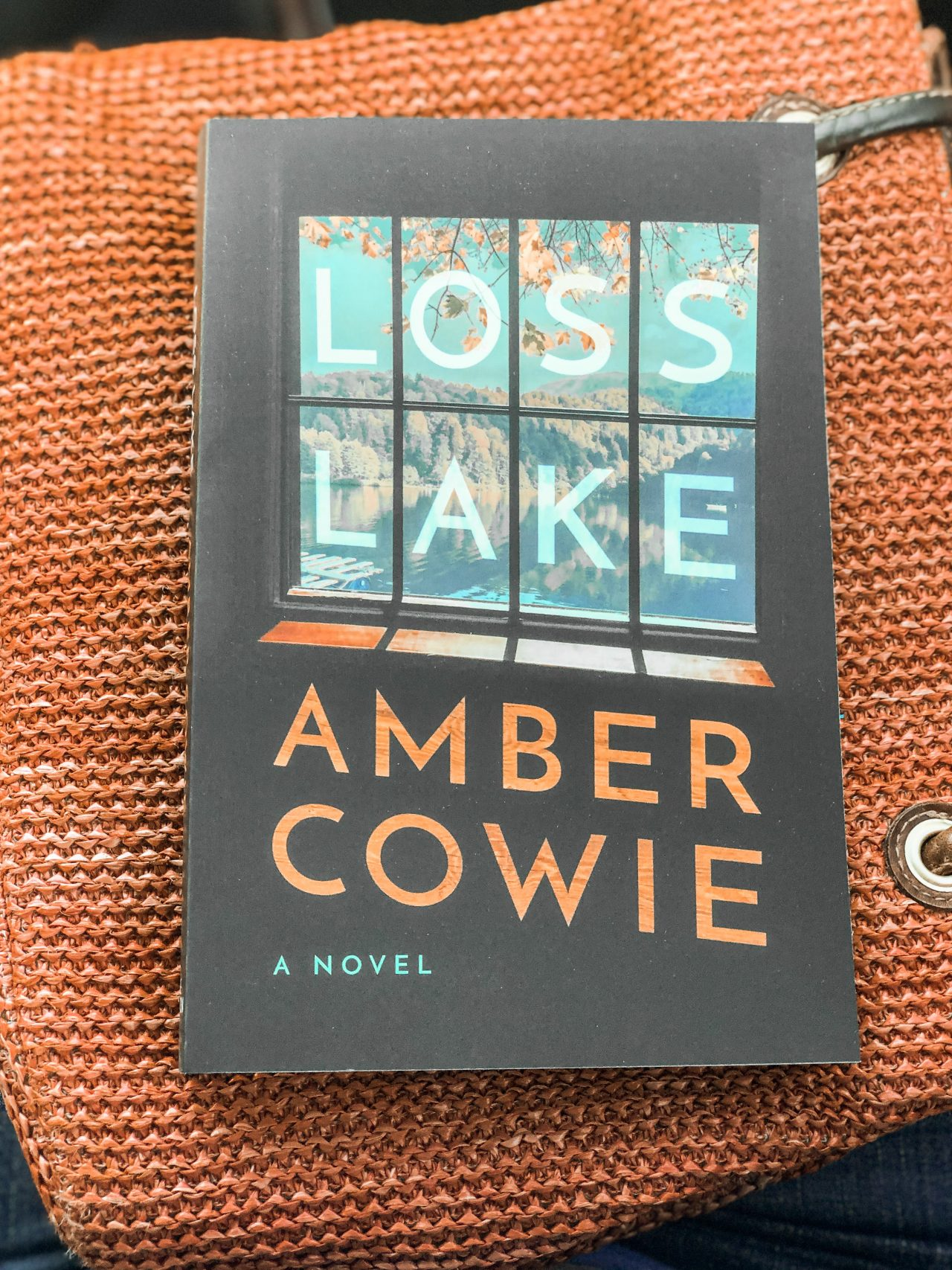 A book with a black cover, a window with glass panes showing a lake, fall leaves hanging from a tree, and tree-covered hills with a bluish-gray sky titled Loss Lake by Amber Cowie